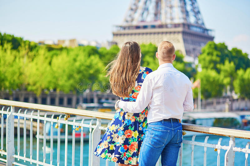 Young romantic couple having a date in Paris. Young romantic couple having a date near the Eiffel tower on a bridge over the Seine in Paris, France royalty free stock photos