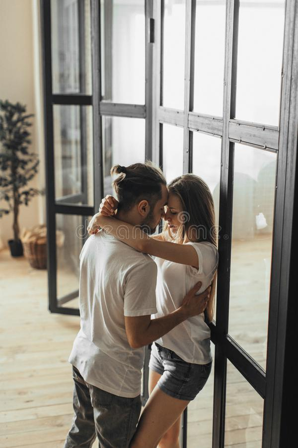 Young romantic couple is kissing and enjoying the company of each other at home stock images