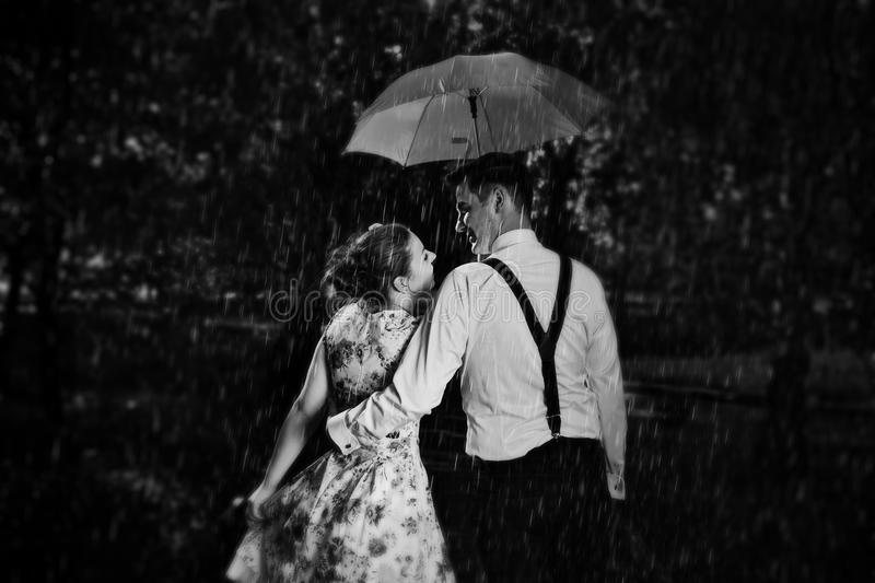 Download young romantic couple in love flirting in rain black and white stock photo