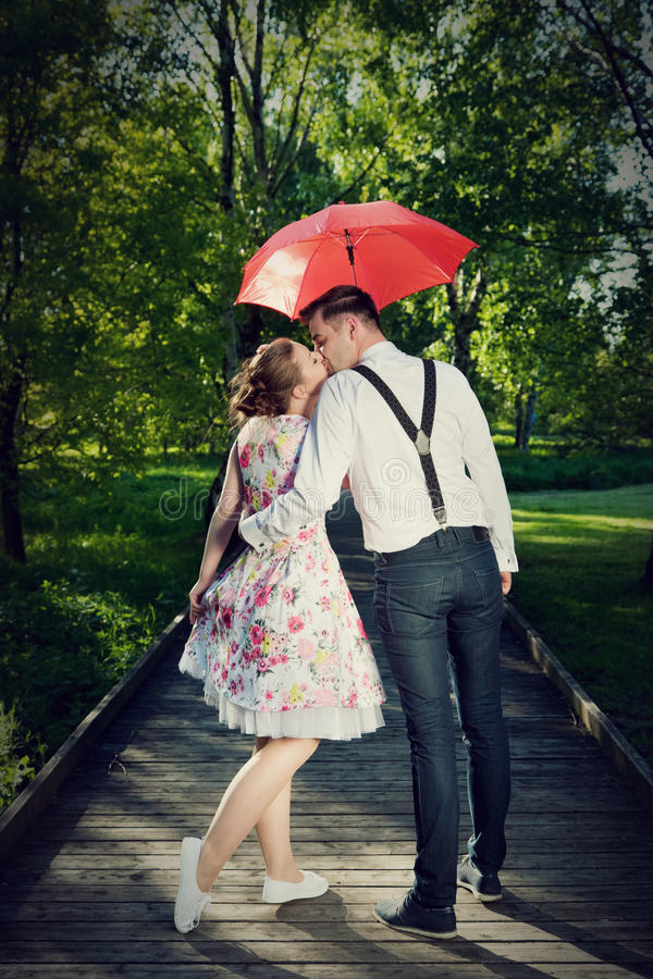 Young romantic couple in love flirting in rain. Red umbrella royalty free stock images