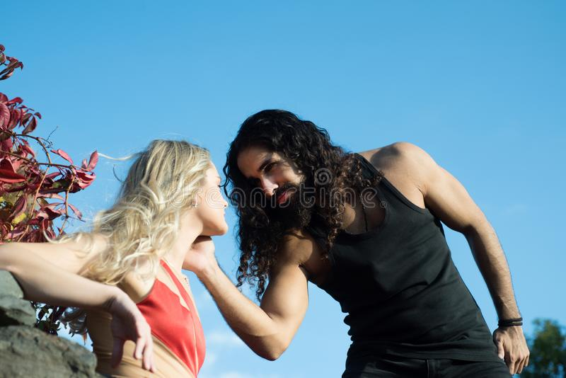 Young romantic couple in love spending time outdoor. Strong handsome bearded man touching his girlfriends neck, looking royalty free stock photo