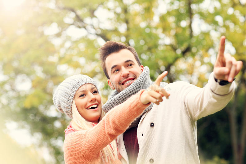 Young romantic couple pointing in the park in autumn royalty free stock photos