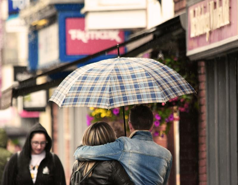 Young romantic couple in the rain. A young couple in the street share an umbrella and a hug as they walk together in a rain shower royalty free stock image