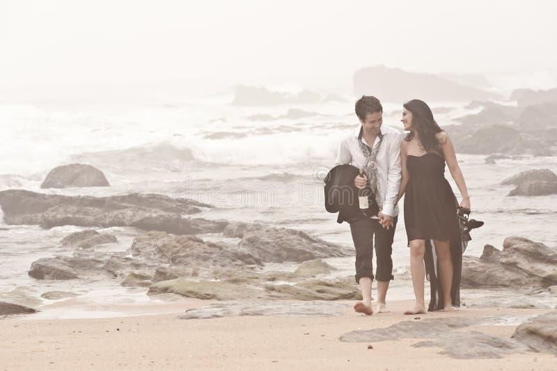 Young romantic couple walking long beach. Through mist royalty free stock photos
