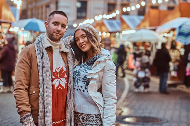 A young romantic couple wearing warm clothes hugging outdoor in evening street at Christmas time, enjoying spending time. A young romantic couple wearing warm royalty free stock photos