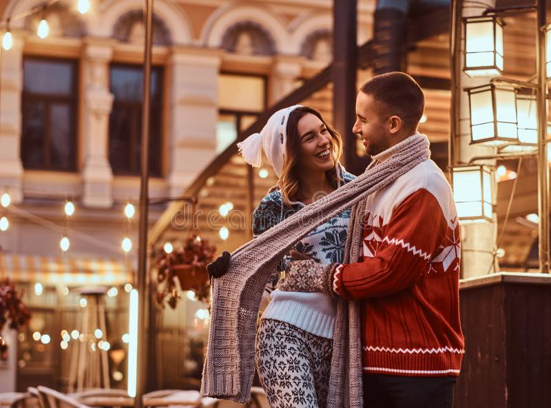 A young romantic couple wearing warm clothes hugging outdoor in evening street at Christmas time, enjoying spending time. A young romantic couple wearing warm royalty free stock images