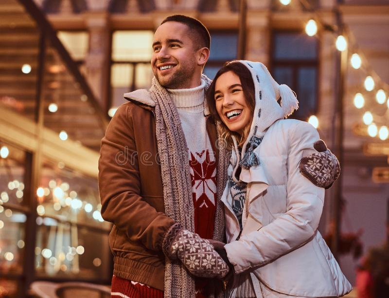 A young romantic couple wearing warm clothes hugging outdoor in evening street at Christmas time, enjoying spending time. A young romantiouple wearing warm stock images