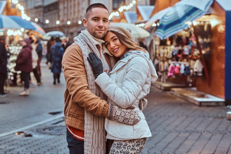 A young romantic couple wearing warm clothes hugging outdoor in evening street at Christmas time, enjoying spending time. A young romantic couple wearing warm stock photo