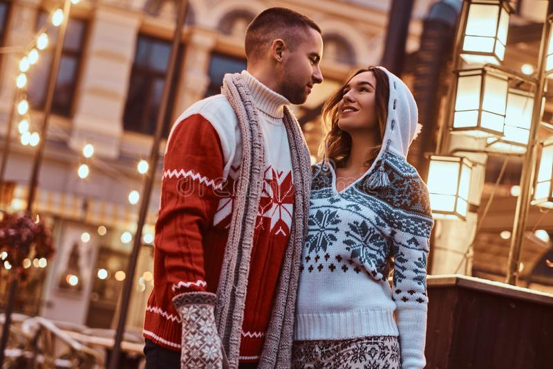 A young romantic couple wearing warm clothes hugging outdoor in evening street at Christmas time, enjoying spending time. A young romantic couple wearing warm royalty free stock photography