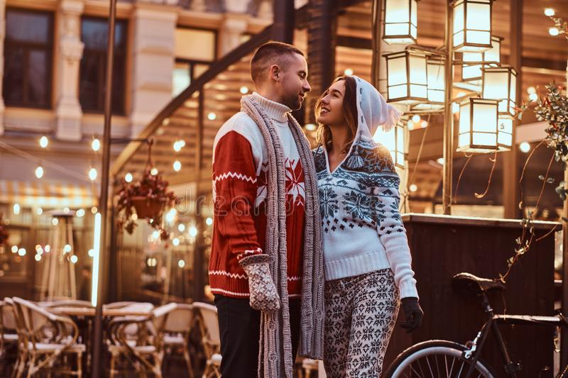 A young romantic couple wearing warm clothes hugging outdoor in evening street at Christmas time, enjoying spending time. A young romantic couple wearing warm royalty free stock photo