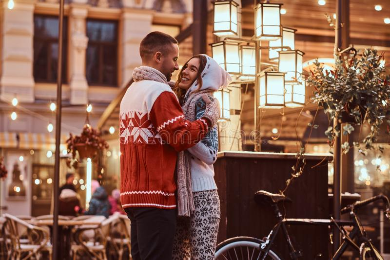 A young romantic couple wearing warm clothes hugging outdoor in evening street at Christmas time, enjoying spending time. A young romantiouple wearing warm stock photography