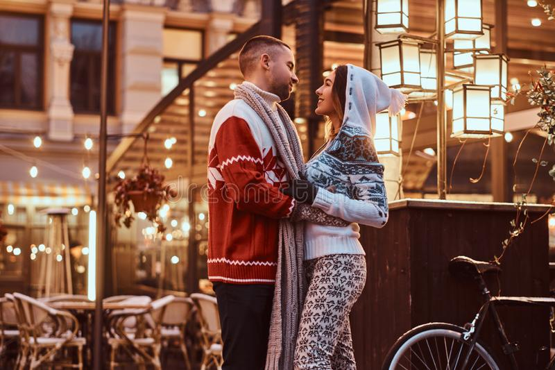 A young romantic couple wearing warm clothes hugging outdoor in evening street at Christmas time, enjoying spending time. A young romantic couple wearing warm stock images