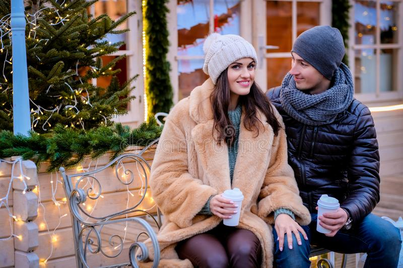 A young romantic couple wearing warm clothes sitting on a bench in evening street decorated with beautiful lights. Romantic couple wearing warm clothes sitting royalty free stock photography