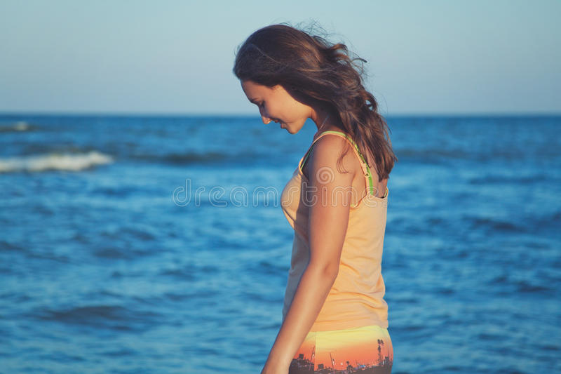 Young romantic girl on beach at sunset royalty free stock images