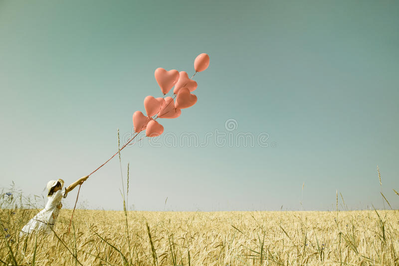 Young romantic girl with red heart balloons walking in a field o. Young romantic girl in summertimes with red heart balloons walking in a field of wheat royalty free stock images