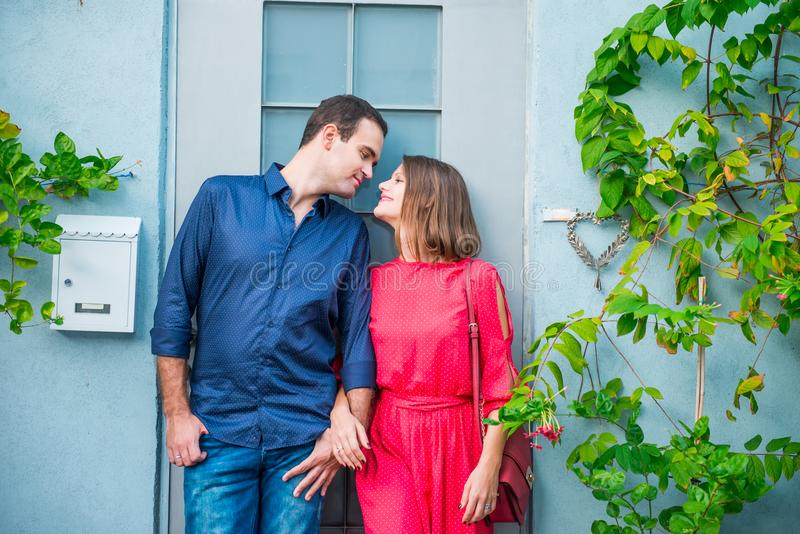 Young romantic married couple in bright clothes standing near their new home house door. Outdoor view of blue house wall with post royalty free stock photography