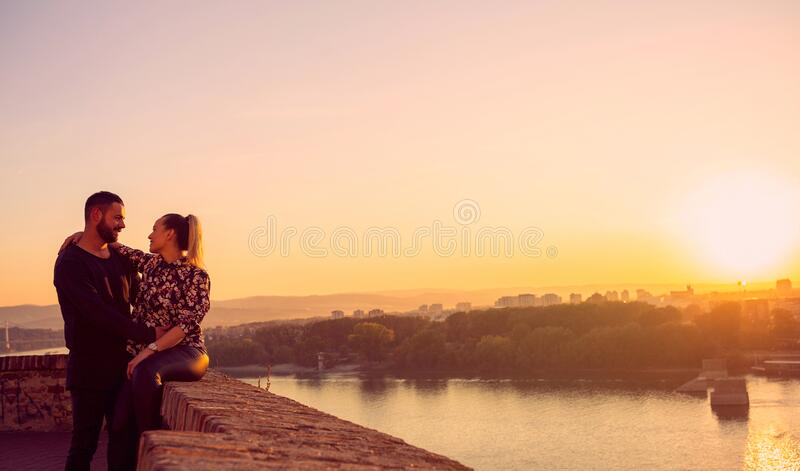 Romantic man and woman spend time together at sunset royalty free stock image