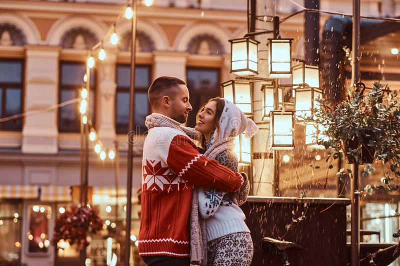 A young romantic couple wearing warm clothes hugging outdoor in evening street at Christmas time, enjoying spending time. A young romantiouple wearing warm royalty free stock photos