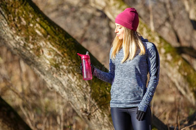Young runner girl with bottle of water in the park. Rehydration concept image with copy space royalty free stock image