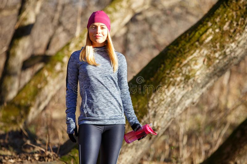 Young runner girl with bottle of water in the park. Rehydration concept image with copy space stock images