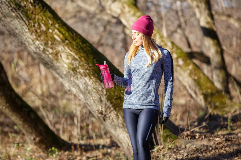 Young runner girl with bottle of water in the park. Rehydration concept image with copy space royalty free stock images