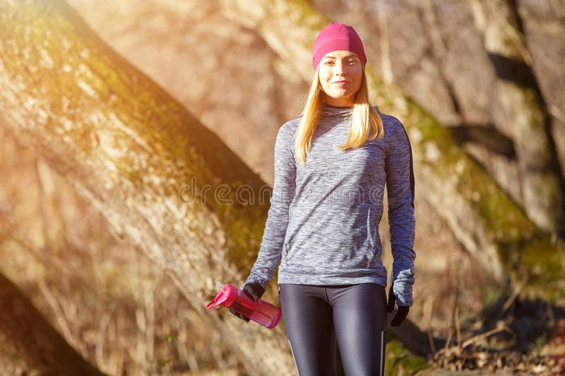 Young runner girl with bottle of water in the park. Rehydration concept image with copy space stock photography