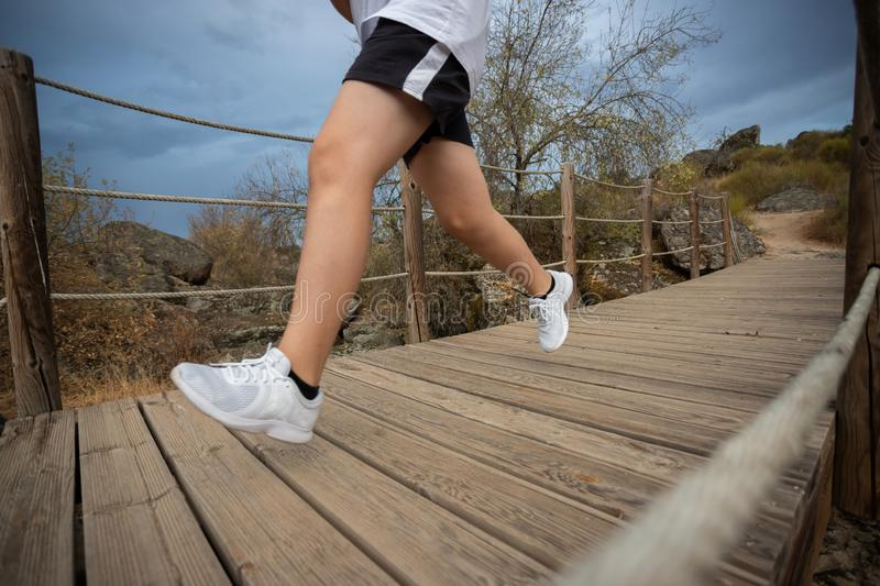 Young runner man running on wood bridge in natural park stock photo
