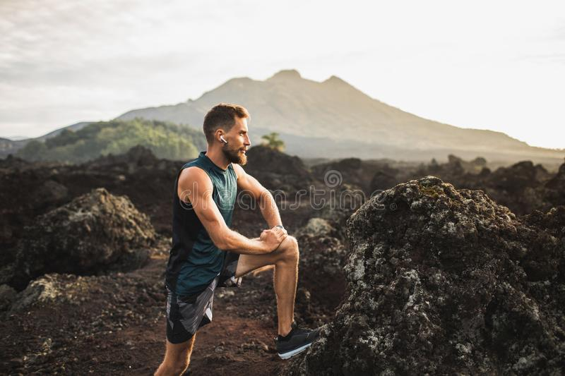 Young runner stretching and warming-up for running. Young hipster runner with beard stretching and warming-up for trail running outdoors. Listening music in air royalty free stock image