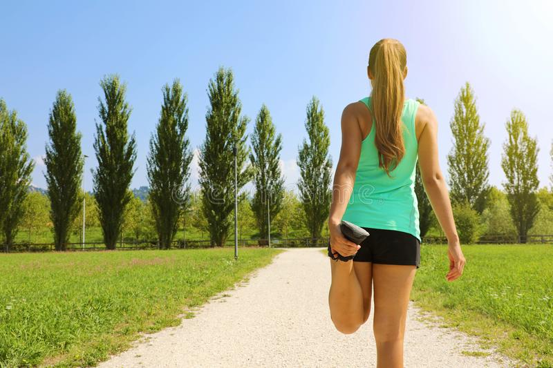Young runner woman doing stretching in the park before run. Copy space.  stock photo
