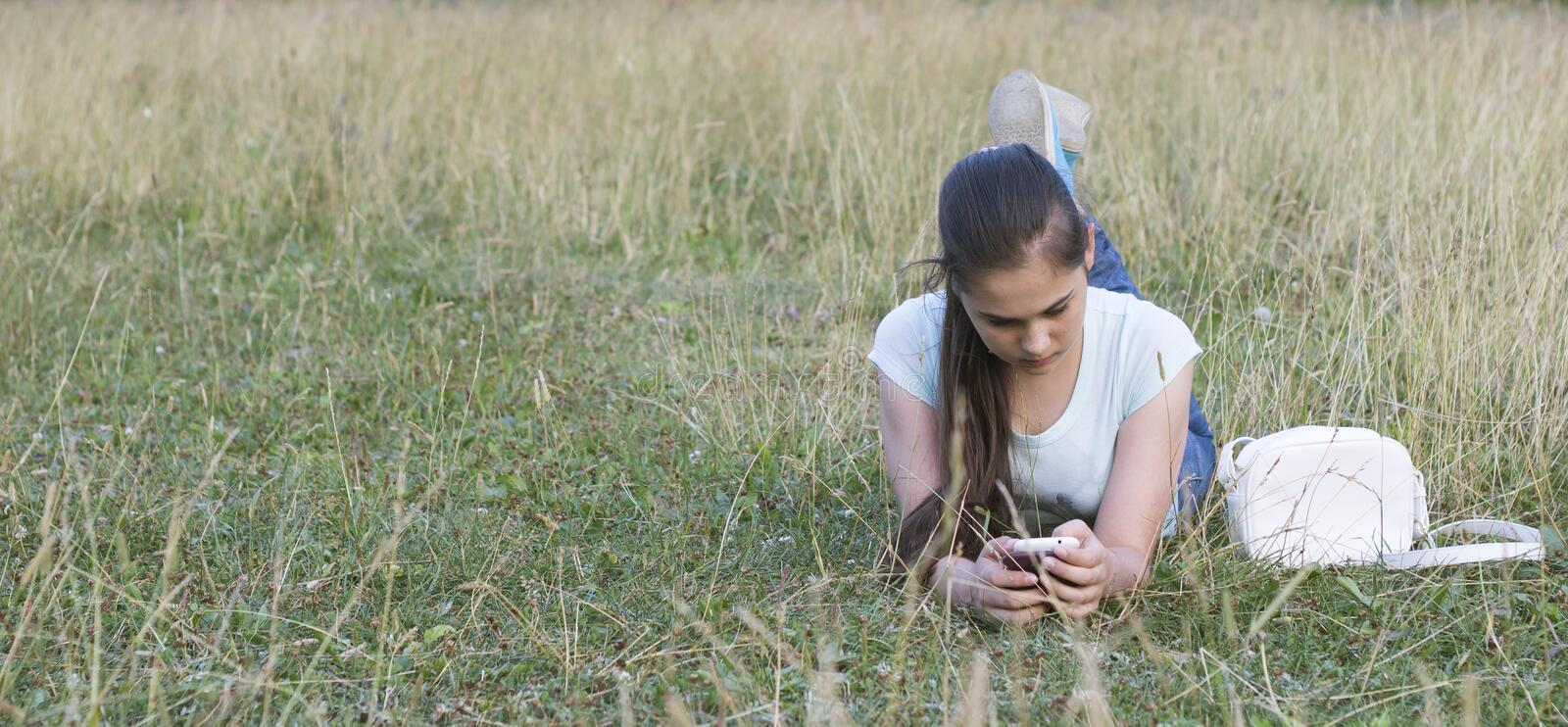 Young sad beautiful woman texting message on mobile phone in urban park - Teenager model girl with worried facial expression hold royalty free stock image