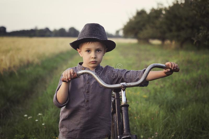 A young, sad boy dressed in a retro style, runs an old bicycle in the countryside. stock photo