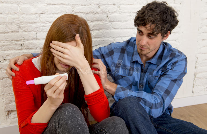 Young sad couple scared with pregnant girl reading pink positive pregnancy test crying overwhelmed. Young sad couple scared in shock and surprise with pregnant royalty free stock photos