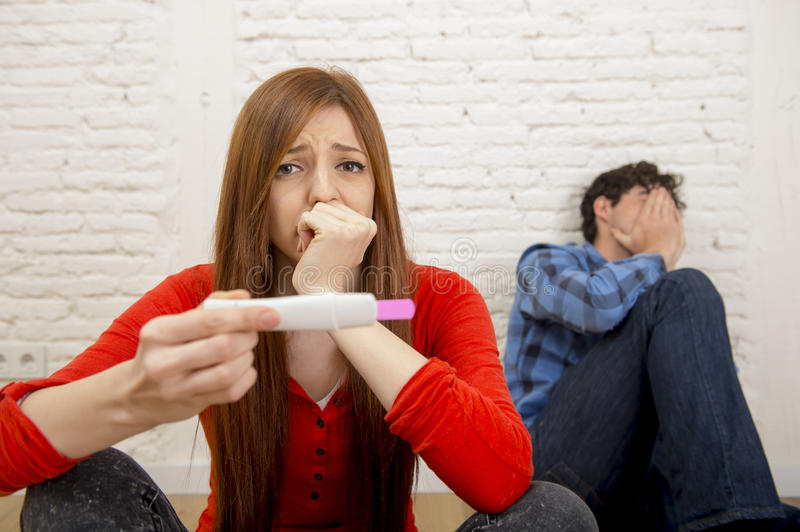 Young sad couple scared in shock and surprise reading pink positive pregnancy test overwhelmed in panic. Young sad couple scared in shock and surprise with royalty free stock image