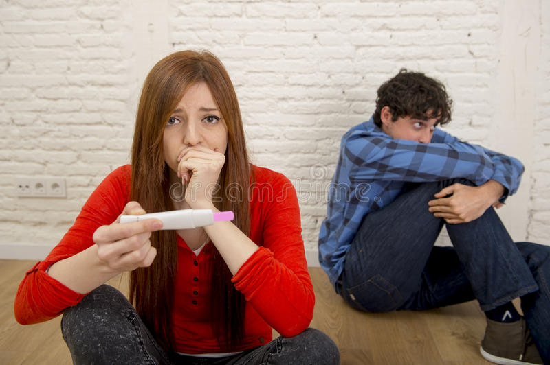 Young sad couple scared in shock and surprise reading pink positive pregnancy test overwhelmed in panic. Young sad couple scared in shock and surprise with stock photos