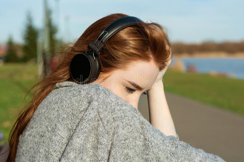 Young, sad cry redhead girl in the spring in the park near the river listens to music through wireless bluetooth headphones.  stock photo