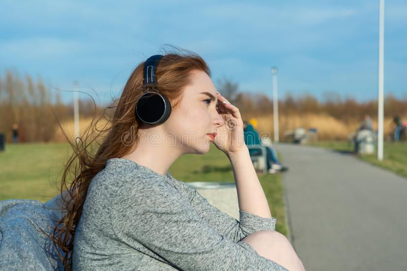 Young, sad cry redhead girl in the spring in the park near the river listens to music through wireless bluetooth headphones.  royalty free stock photography