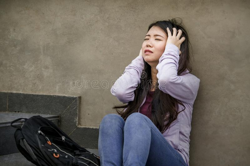 Depressed Asian American student woman or bullied teenager sitting outdoors on street staircase overwhelmed and anxious feeling stock photography