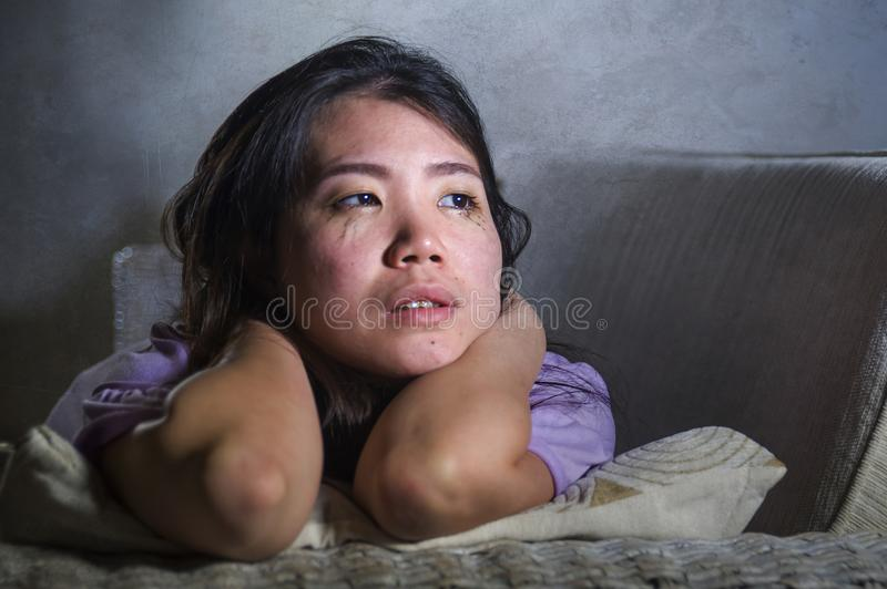 Young sad and depressed Asian Chinese woman at home sofa couch crying desperate and helpless suffering anxiety and depression feel. Ing pain in relationship and royalty free stock image
