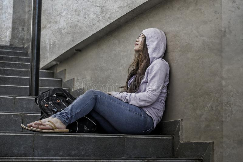 Depressed Asian Japanese student woman or bullied teenager girl sitting outdoors on street staircase victim of bullying feeling. Young sad and depressed Asian stock photos