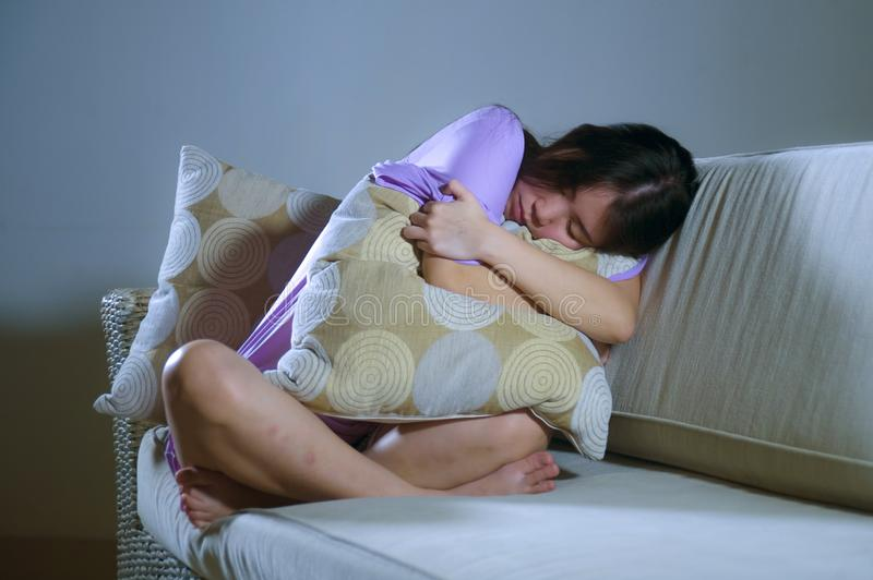 Young sad and depressed Asian Japanese woman crying alone desperate and worried in pain sitting at home sofa couch suffering depre. Ssion and anxiety problem royalty free stock images