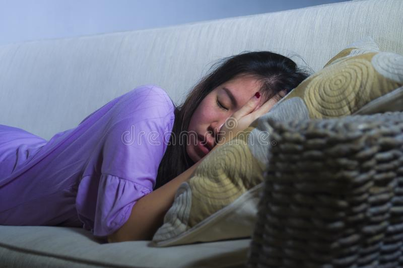 Young sad and depressed Asian Japanese woman crying alone desperate and worried in pain sitting at home sofa couch suffering depre. Ssion and anxiety problem royalty free stock photography