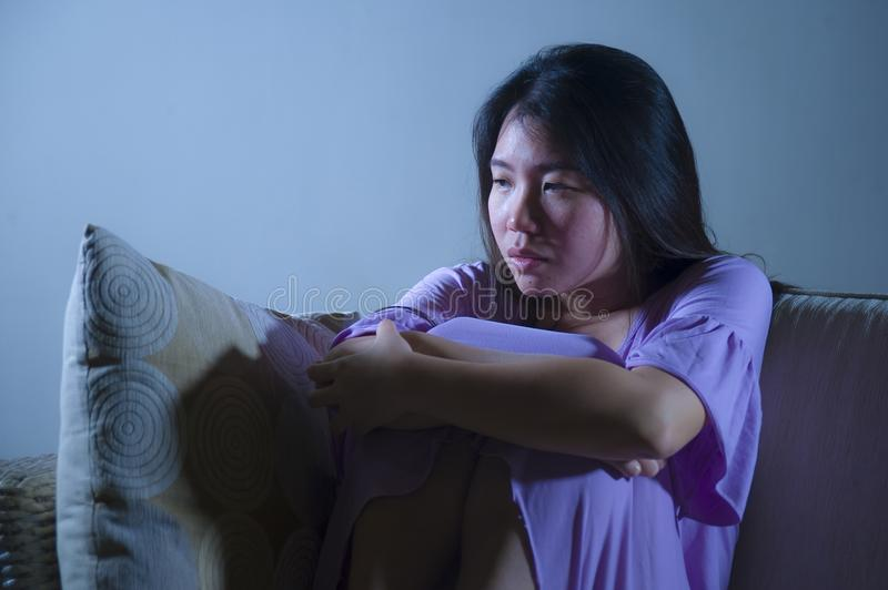 Young sad and depressed Asian Japanese woman crying alone desperate and worried in pain sitting at home sofa couch suffering depre. Ssion and anxiety problem stock images