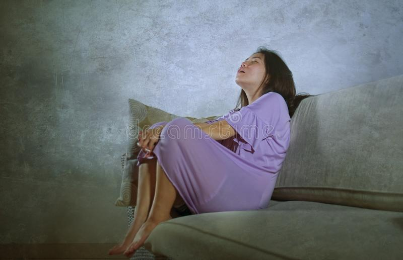 Young sad and depressed Asian Korean woman crying alone desperate and worried in pain sitting at home sofa couch suffering depress. Ion and anxiety problem royalty free stock photos