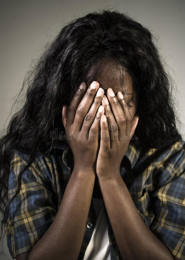 Young sad and depressed black African American woman crying anxious and overwhelmed feeling sick and stressed on studio b royalty free stock image