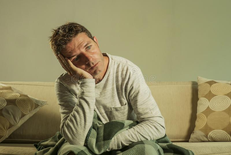 Young sad and desperate man at home sitting at sofa couch suffering depression and anxiety feeling miserable looking thoughtful in. Young sad and desperate man royalty free stock photo