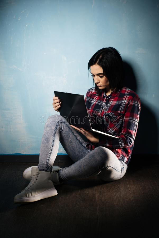 Young sad girl suffering from dependence on social networks sitting on the floor with a notebook stock photo