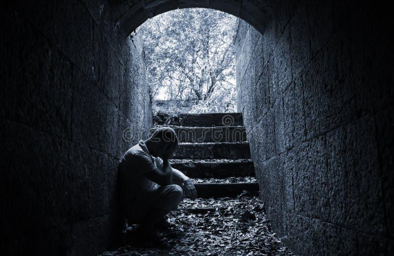 Young sad man sitting inside of dark stone tunnel royalty free stock image
