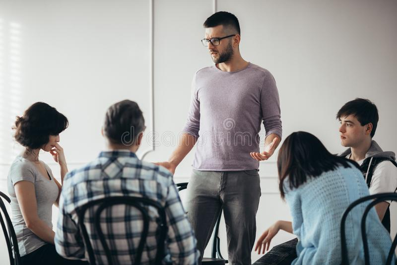 Young sad man talking to the people during psychotherapy. Young sad men talking to the group of people during psychotherapy royalty free stock image