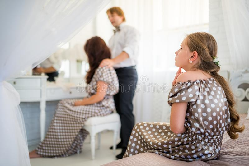 Young sad teenager girl in brown polka-dot dress. Sits on the bed and is jealous of loving blurred parents cuddling on the background. Concept of foster stock photos