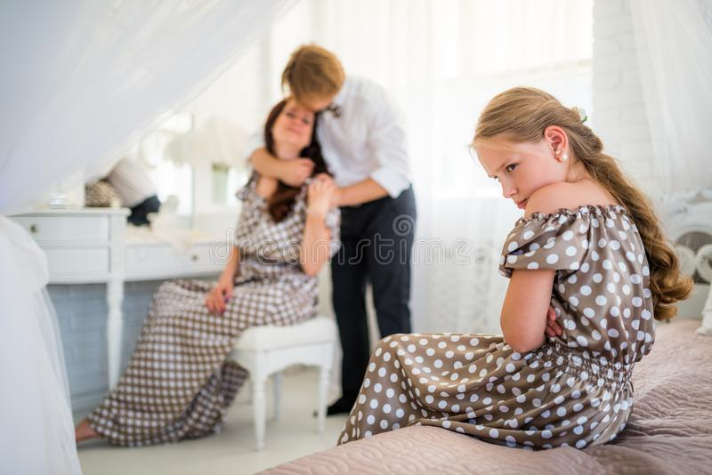 Young sad teenager girl in brown polka-dot dress. Sits on the bed and is jealous of loving blurred parents cuddling on the background. Concept of foster stock photo